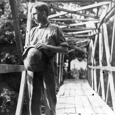 Archival photo of Asheville Farm School boy on a bridge